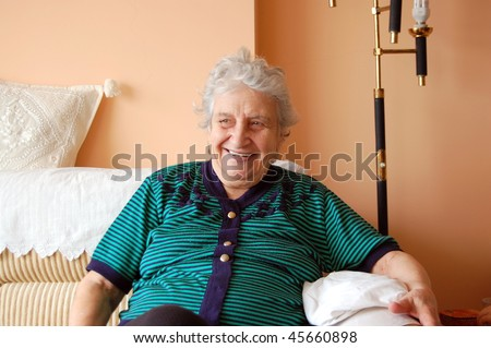 portrait of a sweet retired friendly old woman sitting on a couch