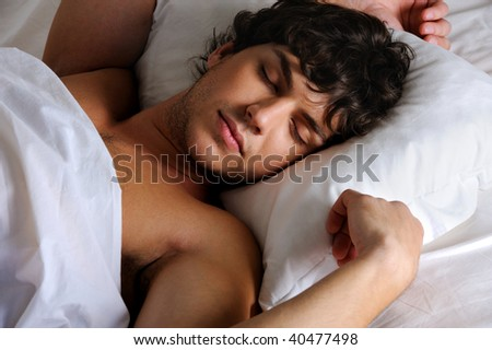 Portrait of a sweet sleeping young beautiful   man lying on back