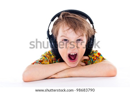 Portrait of a sweet young boy listening to music on headphones against white background