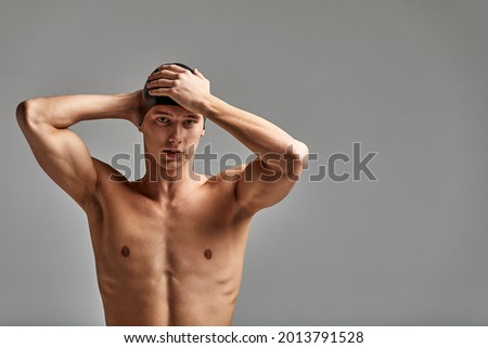 Portrait of a swimmer in a cap, half-length portrait, young athlete swimmer wearing a cap, copies of space, gray background Foto d'archivio ©