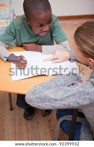 Portrait of a teacher explaining something to a schoolboy in a classroom