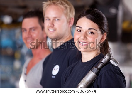 Portrait of a team of mechanics with a woman in the forground
