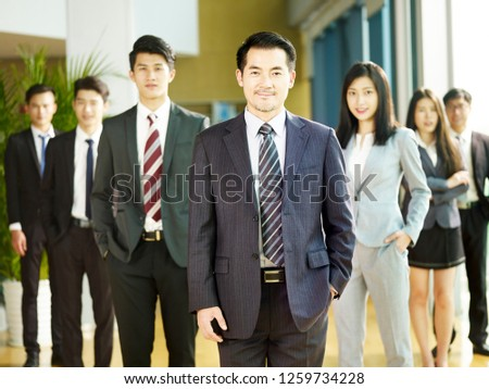 portrait of a team of successful asian businessmen and businesswomen, looking at camera.