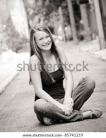 portrait of a teen girl sitting in street in black and white
