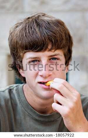 Portrait of a teenage boy eating a french fry