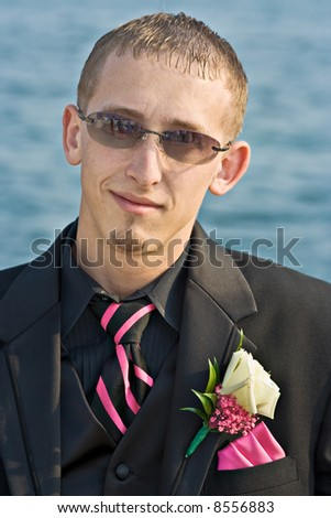 Portrait of a teenage boy in a tuxedo. Background is a blue ocean. The teen is dressed for a high school prom but the photo could be used to represent any formal occasion.