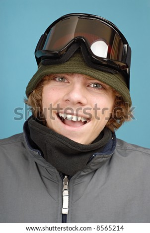 Portrait of a teenage snowboarder in all the winter gear and goggles