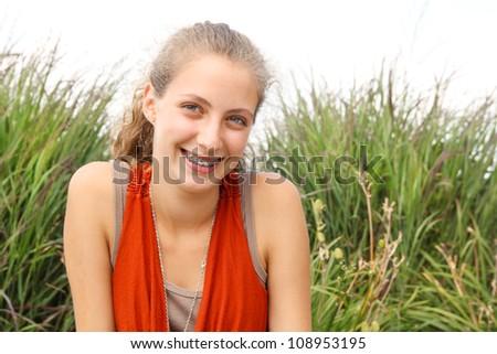 Portrait of a teenager a huge smile wearing an orange shirt