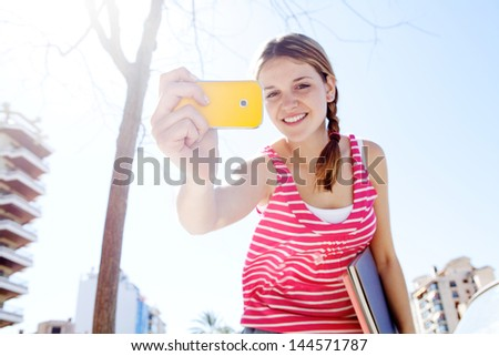 Portrait of a teenager girl using with her colorful smartphone to take photos in the city during a sunny day with a blue sky, smiling.