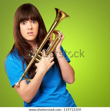 portrait of a teenager holding trumpet on green background