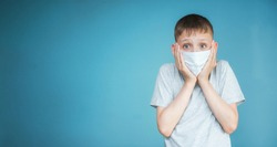 Portrait of a teenager in a t-shirt. Photo of a young boy on a blue background. He is in a medical mask, scared, hands clasped to his face. The concept of virus, caution, fear, panic. Copy space