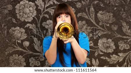 portrait of a teenager playing trumpet, indoor