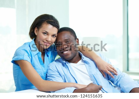 Portrait of a tender African-American couple cuddling at home