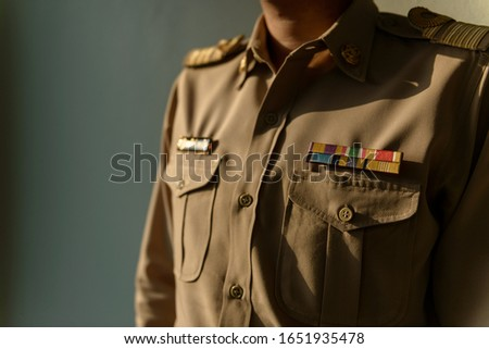 Portrait of A Thai adult man of Thai Government Officer, Civil Servant wears formal Brownish-Yellow uniform.