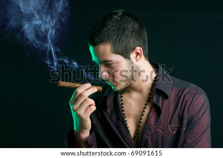 Portrait of a thinking friendly young man with cigar and smoke, studio shot