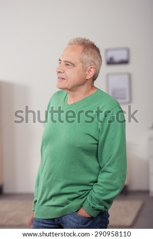 Portrait of a Thoughtful a Middle Aged Man in Casual Clothing, Standing Inside the House While Looking Into Distance with Hand on his Pocket