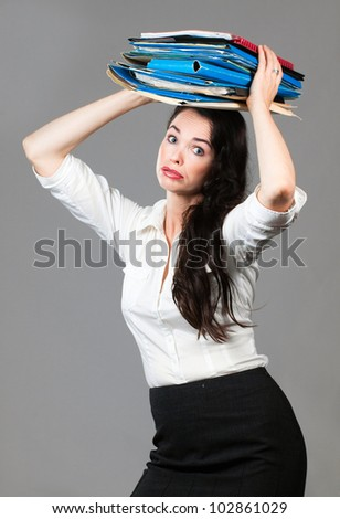 Portrait of a tired and overworked business woman carrying paperwork on her head