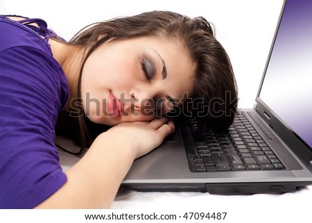 Portrait of a tired brunette sleeping on her laptop
