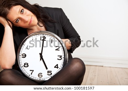 Portrait of a tired woman sitting on the floor while holding a clock
