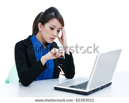 Portrait of a tired young businesswoman with laptop and her hand on head over white background.