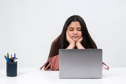 Portrait of a tired young Indian girl resting her chin in her palms with her eyes closed as she sits infront of her laptop