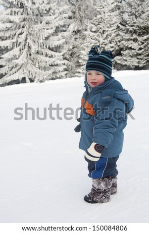 Portrait of a toddler child, boy or girl, i playing in a fresh snow.