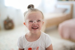 Portrait of a toddler girl in glasses with down syndrome in a bright room, concept for children with disabilities and visual impairment