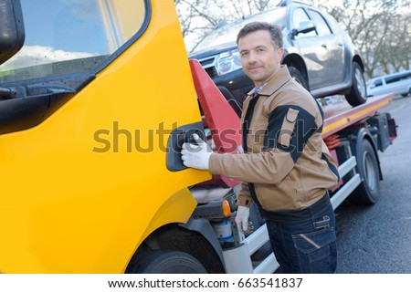 portrait of a tow truck woker with a towed car