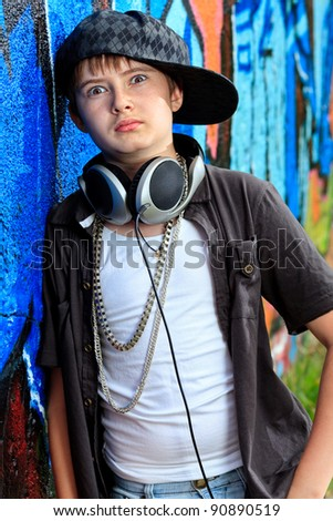 Portrait of a trendy boy teenager with headphones outdoors.