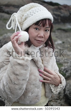 stock photo : Portrait of a Trendy Mature Chinese woman posing on the beach ...