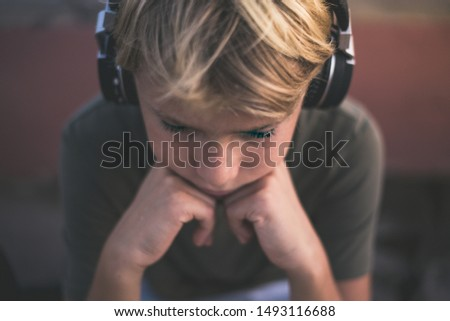 Portrait of a trendy teen enjoying the sound with headphones. Beautiful boy with earphones relax alone listening music.  Teenager playing his rock playlist. Youth, recreation, loneliness concept. #1493116688