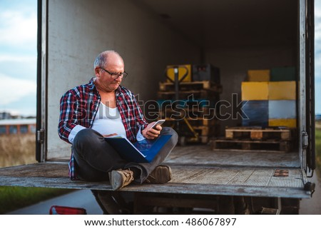 Portrait of a truck driver reading a document and looking at the phone. #486067897