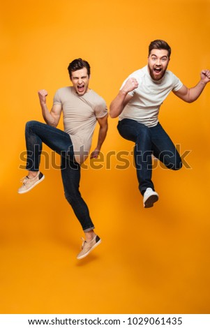 Portrait of a two cheerful young men jumping and celebrating isolated over yellow background