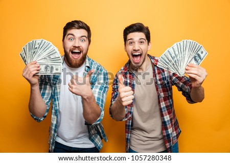 Portrait of a two cheerful young men showing money banknotes and giving thumbs up isolated over yellow background