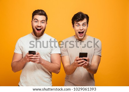 Portrait of a two delighted young men holding mobile phones isolated over yellow background #1029061393