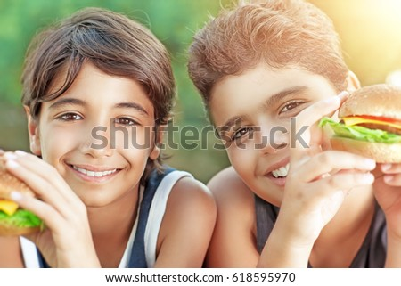Portrait of a two happy boys eating hamburgers outdoors, cheerful teens enjoying unhealthy but delicious food, picnic on sunny day  #618595970