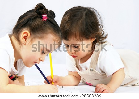 portrait of a two happy pretty girls with a pencils - stock photo