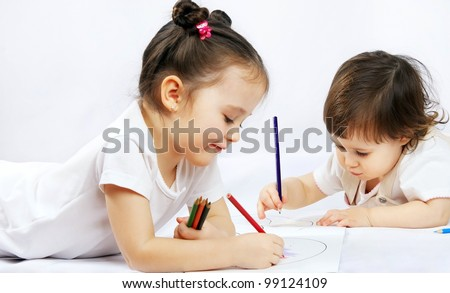portrait of a two happy pretty girls with a pencils