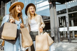 Portrait of a two happy women with shopping bags, standing together in front of the shopping mall