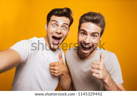 Portrait of a two happy young men best friends showing thumbs up taking a selfie isolated over yellow background #1145329442
