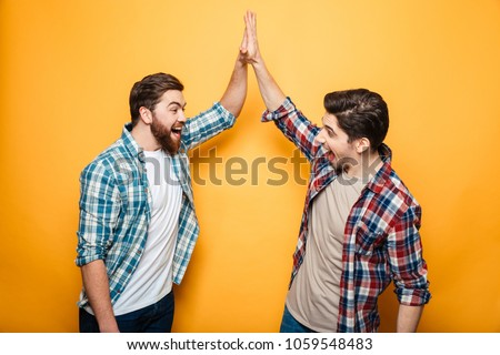 Portrait of a two happy young men giving high five isolated over yellow background