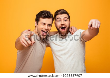 Portrait of a two happy young men pointing fingers at camera isolated over yellow background