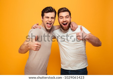Portrait of a two happy young men showing thumbs up isolated over yellow background #1029061423
