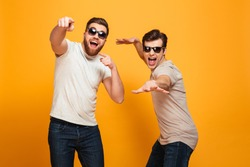 Portrait of a two joyful young men in sunglasses pointing fingers at camera isolated over yellow background