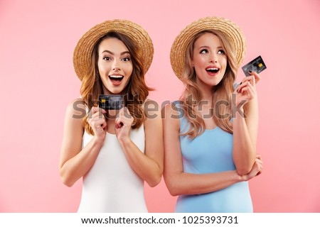 Portrait of a two satisfied girls dressed in swimsuits and summer hats holding credit cards isolated over pink background #1025393731