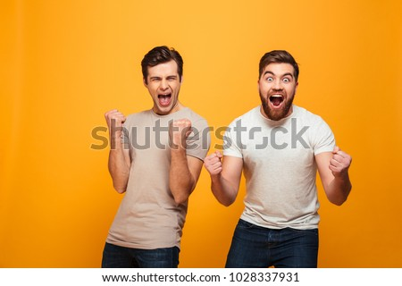 Portrait of a two satisfied young men celebrating isolated over yellow background