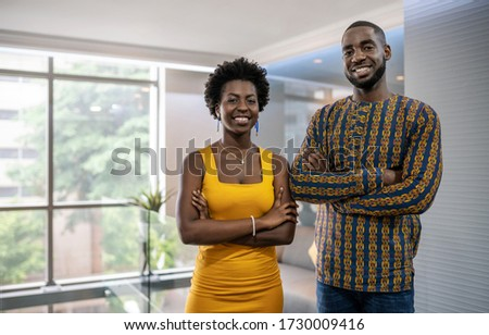 Portrait of a two smiling young African businesspeople standing confidently with their arms crossed in a modern office
