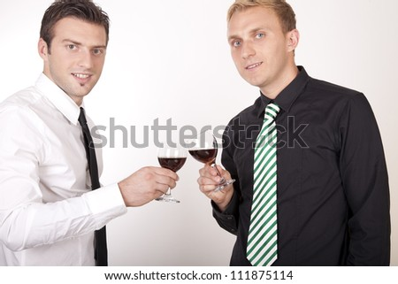 Portrait of a two young attractive businessmen drinking wine.