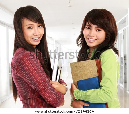 Portrait of a two young students holding a book and smiling