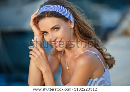 Portrait of a very beautiful sensual and sexy girl in a blue striped dress, on a background of yachts and a summer sea. Close-up